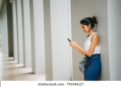 Portrait of attractive and young Indian woman who is dressed professionally. She is standing with grey walls behind her with a smartphone and is looking concerned, worried or upset.
