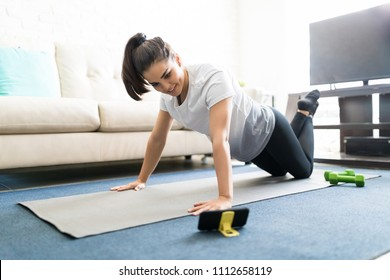 Portrait of attractive young latin woman learning new exercises watching online workout tutorials over her phone at home