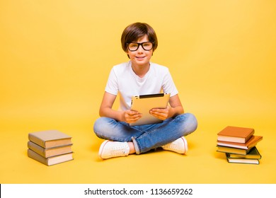 Portrait of attractive young little small cute cheerful school boy, smiling, wearing glasses, holding device over yellow background, books, isolated