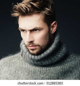 Portrait of an attractive young man with a beard in the studio in a warm sweater