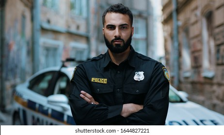 Portrait attractive young man cops stand near patrol car look at camera enforcement happy officer police uniform auto safety security communication control policeman close up slow motion