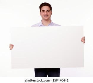 Portrait of an attractive young man holding up a blank placard while standing and smiling at you on isolated background - copyspace