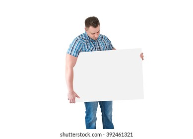 portrait of an attractive young man holding wide blank white card against white background