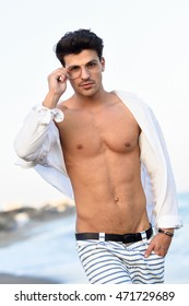 Portrait of an attractive young man on a tropical beach. Handsome guy wearing white shirt and striped shorts. Male with beautiful body and eyeglasses