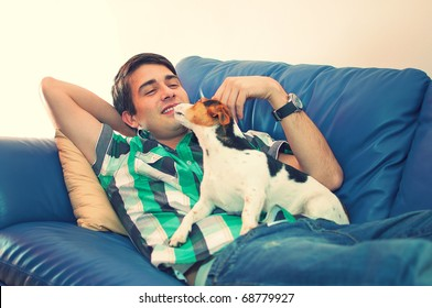 Portrait of an attractive young man playing with his cute dog lying on couch in his living room over white background