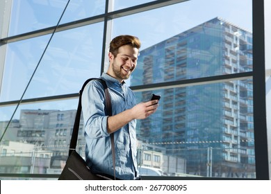 Portrait of an attractive young man walking and looking at mobile phone