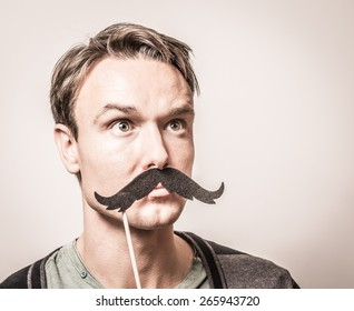 Portrait of an attractive young man wearing a giant retro style fake mustache.