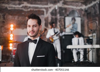 Portrait of an attractive young men, leading to the background playing a cover band. Stylish hairstyle, black bow tie and a white handkerchief in pocket, black suit. Showman, groom smiling