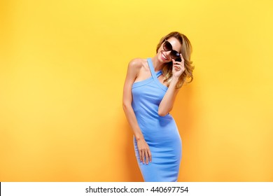 Portrait of attractive young model with blonde hair wearing blue dress against of yellow background.Isolated