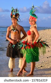 Portrait of attractive young Polynesian Pacific Island Tahitian male and female dancers in colorful costumes on tropical beach during sunset.