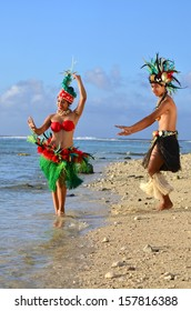 Portrait of attractive young Polynesian Pacific Island Tahitian male and female dancers in colorful costumes dancing on tropical beach during sunset.