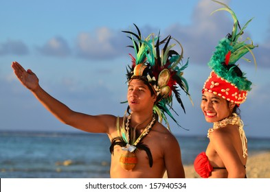 Portrait of attractive young Polynesian Pacific Island Tahitian male and female dancers in colorful costumes on tropical beach during sunset. Real people. Copy space