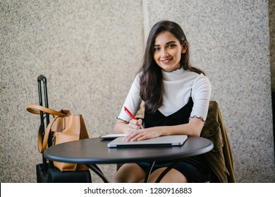 Portrait of an attractive young professional Indian woman, sitting at a desk and writing. She looks relaxed and happy.