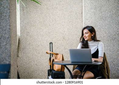 Portrait of an attractive young professional Indian woman, sitting at her desk and working at her laptop. She looks relaxed and happy.