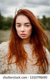 portrait of attractive young red haired  woman posing outdoors