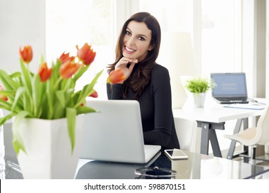 Portrait of an attractive young sales woman working on laptop while sitting at desk in the office.