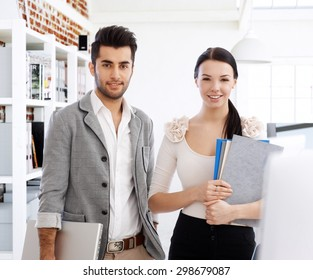 Portrait of attractive young smiling businesspeople, looking at camera.