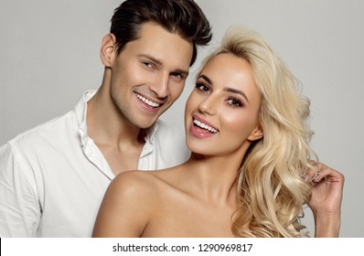 Portrait of attractive young smiling couple isolated over gray background