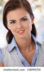 Portrait of attractive young smiling woman, looking at camera.