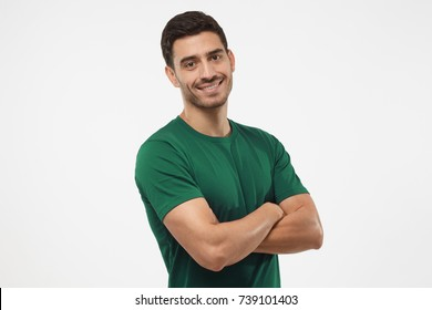 Portrait of attractive young sporty male in green t-shirt standing with crossed arms isolated on gray background. Fitness or crossfit trainer