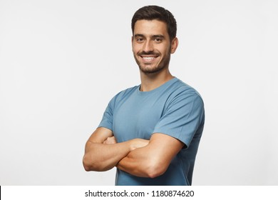 Portrait of attractive young sporty man in blue t-shirt standing with crossed arms isolated on gray background