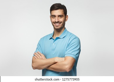 Portrait of attractive young sporty man in blue polo shirt standing with crossed arms, isolated on gray background