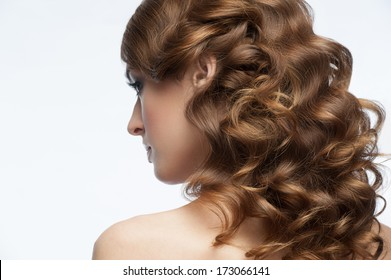 Portrait of attractive young woman with beautiful hairstyle. Girl with long curly hair, rear view