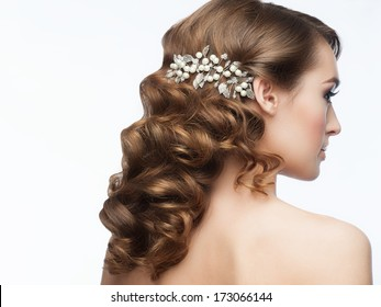 Portrait of attractive young woman with beautiful hairstyle with stylish hair accessory. Girl with long curly hair, rear view