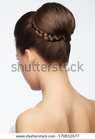 Portrait of attractive young woman with beautiful bridal updo hairstyle with tress, rear view