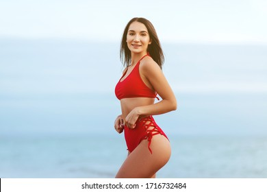Portrait of attractive young woman in bikini on the beach. Young caucasian female model posing in swimsuit on the sea shore and smiling.