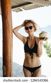 Portrait of attractive young woman with blond dyed short hair in sunglasses drinking coconut milk on the beach. Shielded by sunshade.