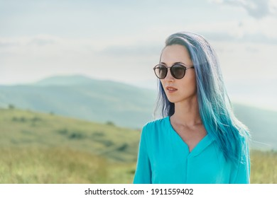 Portrait of attractive young woman with blue hair in sunglasses on nature outdoor.