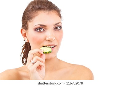 Portrait of an attractive young woman eating a slice of cucumber
