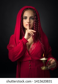 Portrait of attractive young woman in a fancy red dress with copper candlestick and burning candle. Girl with red wavy hair and makeup.