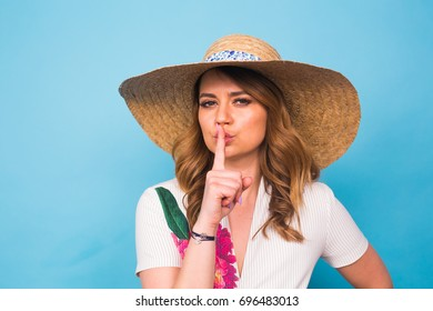 portrait of attractive young woman with finger on lips gesturing silence, studio shot