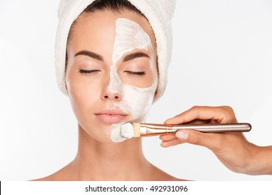 Portrait of a attractive young woman getting beauty skin mask treatment on her face with brush