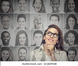 Portrait of an attractive young woman in glasses thinking looking up at a group of multicultural happy people