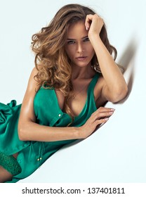 Portrait of attractive young woman in green dress with decolletage