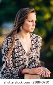 Portrait of Attractive Young Woman Leaning on Ledge Looking into the sun serious