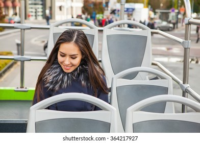 Portrait of attractive young woman with long beautiful hairs in open tour bus,  Luxembourg city.
