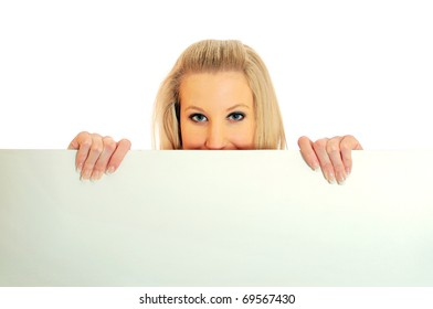 Portrait of an attractive young woman peeping or looking over a white board against white background