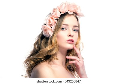 Portrait of attractive young woman with pink flower wreath on head looking at camera.Isolated.