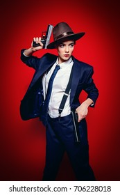 Portrait of an attractive young woman posing in a man's suit and a hat with guns. Gangster style. Man's style clothing. Red background. Fashion shot.