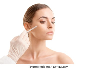 Portrait of an attractive young woman receiving botox treatment. Isolated on white background.