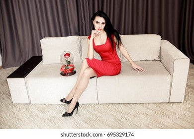 Portrait of attractive young woman in red dress looking at camera and smiling while sitting on the couch at home. Brunette woman with red rose, received as a gift in modern apartment