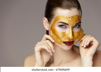 Portrait Of Attractive Young Woman Removing Golden Mask From Smooth Face With Hands.