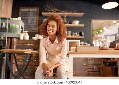 Portrait of an attractive young woman sitting on a chair while working in a cafe