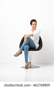 Portrait of attractive young woman sitting in a chair. White shirt and jeans. White floor and white wall in the background