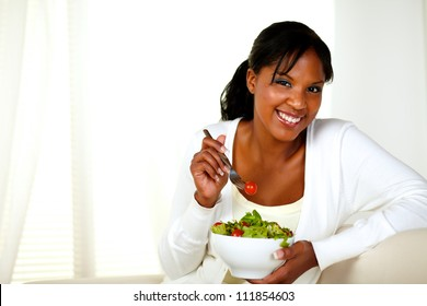 Portrait of a attractive young woman smiling and eating a vegetable salad and looking at you on a light background. With copyspace.
