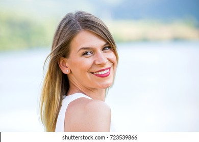 Portrait of an attractive young woman smiling at the camera posing outdoor